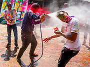12 MARCH 2017 - BHAKTAPUR, NEPAL:  Men use a water hose on each other during Holi celebrations in Bhaktapur. Holi, a Hindu religious festival, has become popular with non-Hindus in many parts of South Asia, as well as people of other communities outside Asia. The festival signifies the victory of good over evil, the arrival of spring, end of winter, and for many a festive day to meet others. Holi celebrations in Nepal are not as wild as they are in India.    PHOTO BY JACK KURTZ