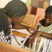 Women use traditional looms to weave textile at the Village Artisanal de Ouagadougou, a cooperative that employs dozens of artisans who work in different mediums, in Ouagadougou, Burkina Faso, on Monday November 3, 2008.