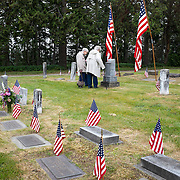Two elderly widows of WWII veterans visit the cemetery where their husbands are both buried. The vets survived the war but not their wives. The two grave stones at upper right are for Civil War veterans who fought for the Union Army. At Sequim View Cemetery, Sequim WA.