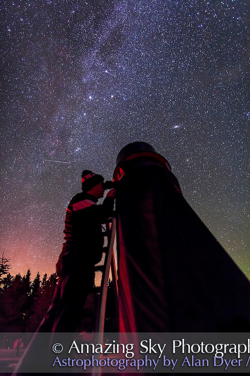 Astronomer Vance Petriew at the eyepiece of his 20-inch Dobsonian reflector telescope, at the 2012 Saskatchewan Summer Star Party in Cypress Hills, SK. This is a single 20 second exposure with the Canon 5DMkII at ISO 4000, and 24mm Canon L-series lens at f/2. A faint aurora adds the horizon colours. The photo was taken on the occasion of the second return of Comet Petriew 185/P since its discovery 11 years earlier in 2001 at this very same location.