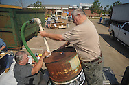 Leroy Young (left) of Young's Oil Service in Oakman, Ala. gets used oil from Lester Michelletti  at the Household Hazardous Waste Collection Day at the Oxford Conference Center in Oxford, Miss. on Saturday, April 9, 2011.