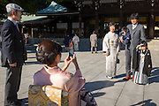 Visitors to the Meiji Shrine, Tokyo take pictures. Many weddings are done there and people often come in traditional Japanese dress.