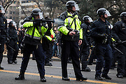 WASHINGTON, USA - January 20: A police officer fires a bean bag round at anti-Trump protestors during clashes after President Trump was sworn into office in Washington, USA on January 20, 2017.