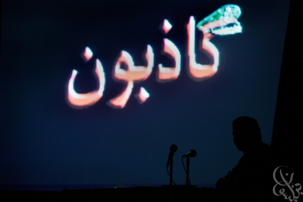"""An Egyptian revolutionary youth council activist is seen silhouetted during a """"Kazeboon"""" film screening at a January 18, 2012 press conference in Cairo, Egypt. """"Kazeboon"""" means """"liars"""" in Arabic, and is a grass rotts Egyptian movement to counter what activists say are anti-revolutionary lies and propaganda from the ruling Supreme Council of Armed Forces (SCAF)."""