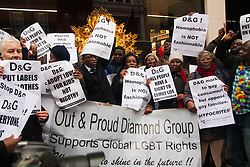"""Mayfair, London, March 19th 2015. Police are called as gay rights campaigners from the Out and Proud Diamond Group, made up of exiled Ugandan and other African gays and their supporters,   demonstrate outside the D&G store in London's Bond Street, following Remarks made by the brand's owners about IVF babies being """"synthetic""""."""
