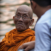 Thai Buddhist monk Luang Pho Malai, 91 years old, chats briefly with a fellow Buddhist Saturday, June 29, 2013, on the outskirts of Bangkok.   For the past 30 years Luang Pho Malai has made his daily round to attend to the faithful in a small wooden boat to collect their offers and dispense blessings.  While many of Bangkok's major canals were filled in and paved over during the building boom of the 1980's klong Thavi Watthana still serves the needs of a impoverished community.