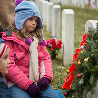 Victoria Whitt, 6, center, looks on at the headstone of Army Capt. Shane Timothy Adcock in Section 60 of Arlington National Cemetery, December 14, 2013 in Arlington, VA. Adcock died on October 11, 2006, in Hawijah, Iraq, from enemy grenade fire. Among the friends and family members, volunteers also placed thousands of remembrance wreaths on headstones around the cemetery during National Wreaths Across America Day.  Photo Ken Cedeno