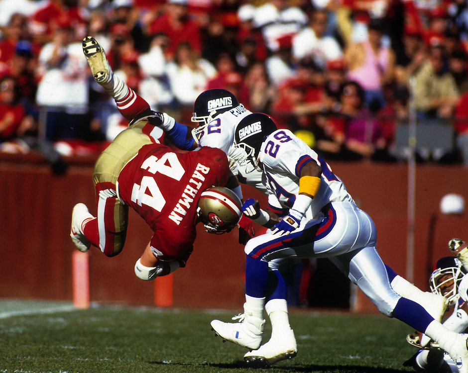 SAN FRANCISCO, CA-1991:  Running back Tom Rathman of the San Francisco 49'ers is upended during the 1991 NFC Championship game against the New York Giants at Candlestick Park, San Francisco, CA.    (Photo by Ron Vesely)