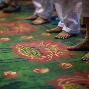 Worshipers stand on the ornately painted  lotus flowers on the floors of the Temple of the Goddess of Mercy in Penang, Malaysia.