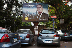 "A billboard in the Dokki area of Cairo shows Amr Moussa standing in front of both mosques and churches, with the text: ""One people, one nation.""."