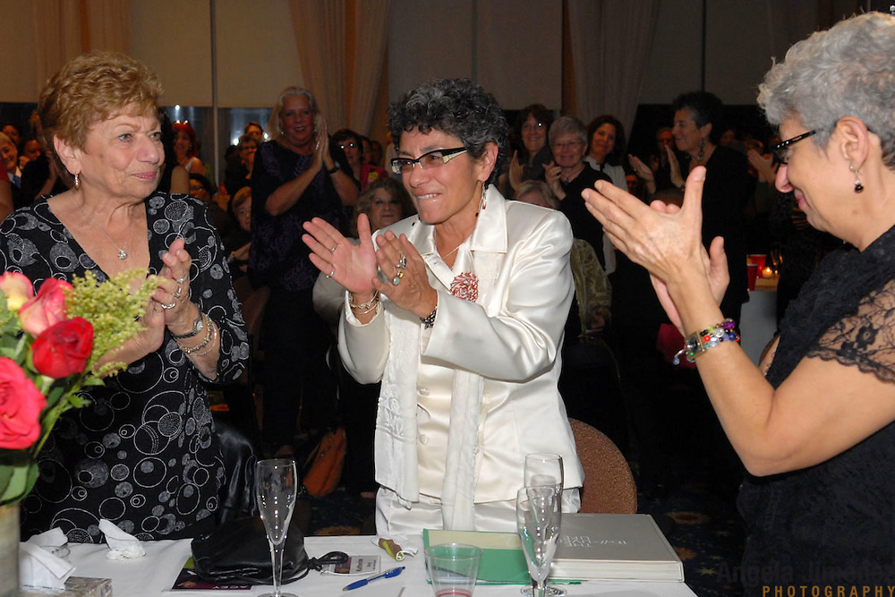 Katherine Acey, center, gets a standing ovation from the crowd, including her aunt Cam A. Centolella, left, and sister JoAnn Acey, right,  during a ceremony/party held to celebrate her 20 years of service as the Executive Director of the Astraea Lesbian Foundation for Justice, at the 1199 penthouse at 330 West 42nd Street in New York City on October 10, 2007. ..Photo by Angela Jimenez.photographer contact:.angelajime@gmail.com.917-586-0916