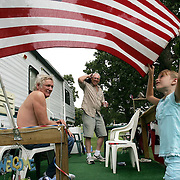 Mandy Martin, 8, from Montezuma, straightens the American flag which had become wrapped around it's flagpole at theIowa State Fairgrounds campsite.  Behind her are Dick Puls, her grandfather from Grinnell, right, and guest Jess Hasley.  Mandy's parents and Puls were the third and fourth campers to enter the grounds Saturday morning at 7 a.m.  They picked an uncharted area overlooking the fairgrounds.  The family plans to spend three weeks at the campgrounds.  Puls will be attending his 50th fair.