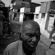 Suffering from asbestosis and having a hard time breathing 66-year-old Mangabhai Patel is seen walking to the local temple in Ahmedabad, India. He worked for 37 years at the Ahmedabad Electric Company (AEC) and was exposed to asbestos and has been diagnosed with Asbestosis. He is constantly gasping for air due to his severely damaged lungs. He can only walk short distances before he is nearly incapacitated from the disease which causes difficulty in breathing. After 10 years of trying to get compensation, an out of court settlement of approximately $4000.00 dollars will be paid to him in compensation.