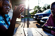 """Ellen """"El"""" Wilson talks with neighbors in front of Hoover's Convenience store in the Baptist Town neighborhood of Greenwood, Mississippi on Wednesday, April 21, 2010."""