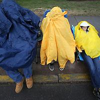 (Wellesley, MA - 4/20/15) Cousins Matthew Sahagian, 15, Cody Delvecchio, 15, and Travis Delvecchio, 12, huddle under ponchos while waiting for the Boston Marathon to begin, Monday, April 20, 2015. Staff photo by Angela Rowlings.
