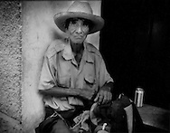 Old man props himself up in a corner of a shop entrance in the southern border town of Tapachula, Mexico.