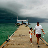 ANNA MARIA ISLAND, FL -- July 9, 2009 -- Matt Danahy and his daughter, Lauren, 8, of Tampa head away from a fast approaching storm at the Rod & Reel Pier on Anna Maria Island in Manatee County, Fla., on Thursday, July 9, 2009.  (Chip Litherland for The New York Times)