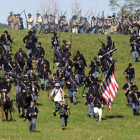 Confederate troops, top, advance on retreating Union soldiers during a  reenactment of Maney's Attack, during the weekend-long Battle of Perryville,  a national Civil War Reenactment, in Perryville, Ky., on 10/5/02. Maney's  Attack represents the attack of Geneeral George Maney's Confederate Brigade  against Terrill's and Starkweather's Union Brigades through a cornfield,  considered to be one of the heaviest fights in the battle.