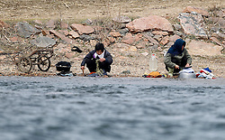 North Korean women are seen doing their laundry along North Korean bank of the Yalu River near the town of Sinuiji across the Chinese city of Dandong, Liaoning Province, China on 06 April 2013. North Korean leader Kim Jong-un has ordered the country's military to increase artillery production, a televised report out of Pyongyang showed 06 April.