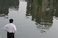 HIROSHIMA A-BOMB 60TH ANNIVERSARY. On the morning of the 60th anniversary a man stands alone with his thoughts beside the river, in which is reflected the A-Bomb Dome which survived the August 6th 1945 atomic bombing of Hiroshima. The dome is now a memorial. Hiroshima, Japan. 06.08.05