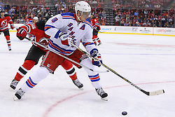 Oct 21, 2014; Newark, NJ, USA; New York Rangers defenseman Marc Staal (18) plays the puck while being defended by New Jersey Devils center Adam Henrique (14) during the second period at Prudential Center.