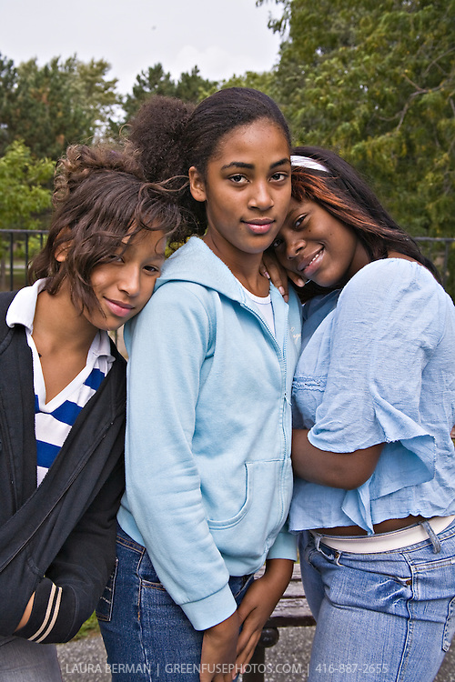 A group of African-American teenage girls posing, with attitude. One girl is in the center while her two friends lean on either side of her. Their closeness and friendship is evident in their attitudes.
