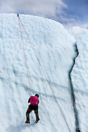 Ice climber scaling terminus of Matanuska Glacier in Southcentral Alaska. Spring. Afternoon.