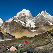 Sunrise hits the Cordillera Huayhuash above Carhuacocha lake campground (13,600 feet) in the Andes Mountains, Peru, South America. Peaks from left to right are: Siula Grande, Yerupaja Grande (6635 m or 21,770 ft, highest point in the Amazon watershed), Yerupaja Chico, and Mount Jirishanca (Icy Beak of the Hummingbird). Day 3 of 9 days trekking around the Cordillera Huayhuash. This panorama was stitched from 4 overlapping photos.