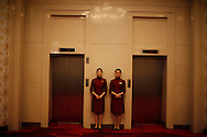 Chinese attendants wait outside elevators at Great Hall of the People  in Beijing, China, Tuesday, Sept. 29, 2009. The Great Hall of the people's with it's impressive Stalinist building style and attention to protocol remains as one of the the country's last showcases  of old style communism on a grand scale.