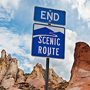 """END SCENIC ROUTE"" sign marks the end of the park road but beginning of the spectacular White Domes trail in Valley of Fire State Park, Nevada, USA. Starting more than 150 million years ago, great shifting sand dunes during the age of dinosaurs were compressed, uplifting, faulted, and eroded to form the park's fiery red sandstone formations. The park also boasts fascinating patterns in limestone, shale, and conglomerate rock. The park adjoins Lake Mead National Recreation Area at the Virgin River confluence, at an elevation of 2000 to 2600 feet (610-790 m), 50 miles (80 km) northeast of Las Vegas, USA. Park entry from Interstate 15 passes through the Moapa Indian Reservation."
