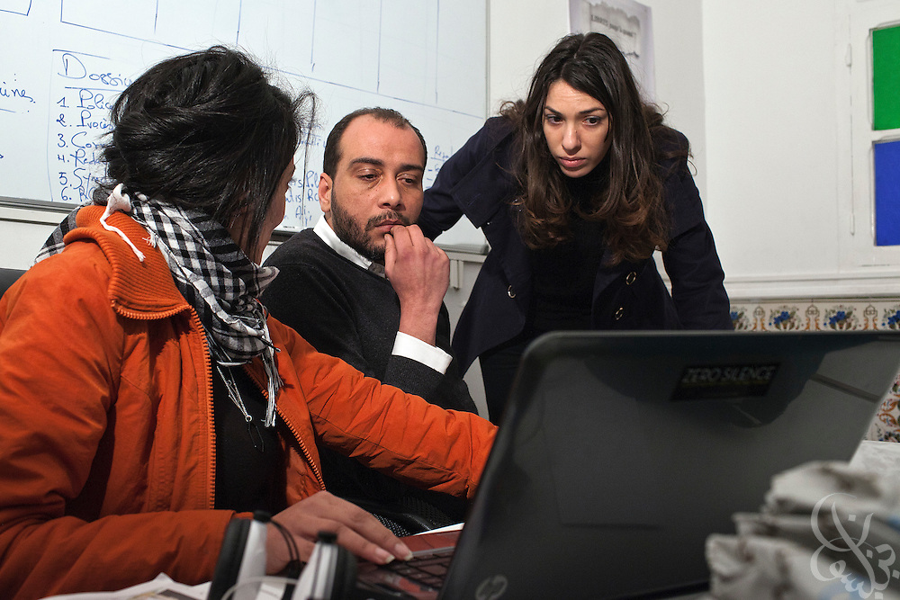 Nawaat co-founder Malek Khadhraoui (c) and Nawaat blogger Emna el Hammi (r) work in the groups headquarters March 05, 2012  in Tunis, Tunisia. Nawaat.org is an independent group blog that supports political transparency civil state building and press freedom.