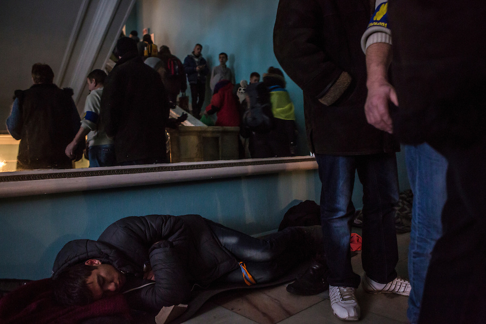 KIEV, UKRAINE - DECEMBER 7: A man sleeps on a stair landing as other anti-government protesters walk past in the occupied International Centre of Culture and Arts on December 7, 2013 in Kiev, Ukraine. Thousands of people have been protesting against the government since a decision by Ukrainian president Viktor Yanukovych to suspend a trade and partnership agreement with the European Union in favor of incentives from Russia. (Photo by Brendan Hoffman/Getty Images) *** Local Caption ***