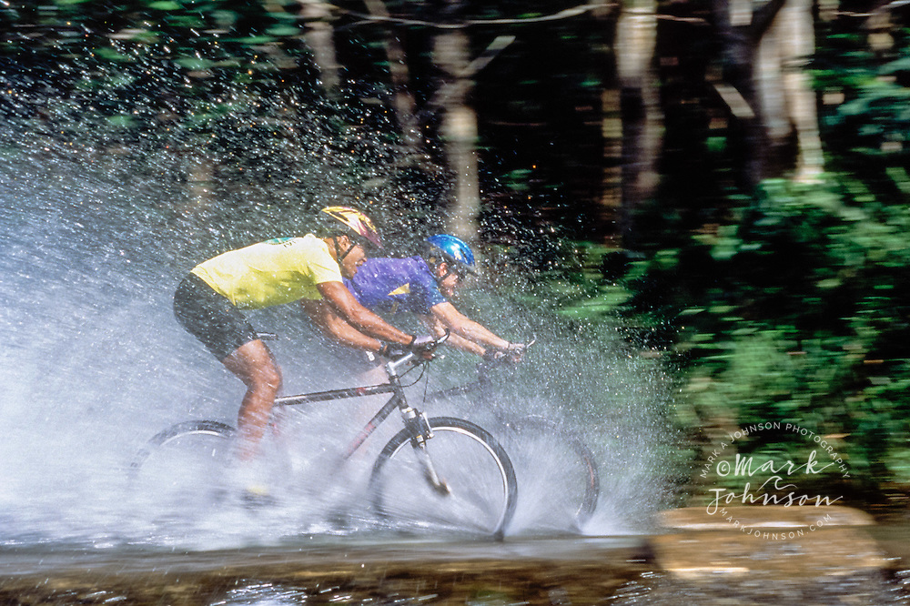 Mountain bikers splashing through water, Kauai, HI