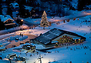 Winter view of skiers and snowboarders surrounding the Daylodge at Alyeska Resort in Girdwood Alaska during the holiday season