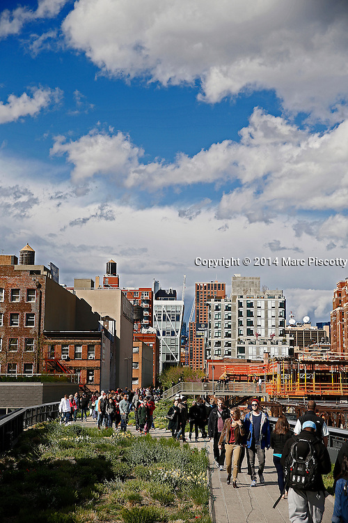 SHOT 5/4/14 2:29:36 PM - Locals and tourists stroll along the High Line in New York City, N.Y. The High Line (also known as the High Line Park) is a 1.45-mile-long New York City linear park built in Manhattan on an elevated section of a disused New York Central Railroad spur called the West Side Line. Inspired by the 3-mile (4.8-kilometer) Promenade plantée, a similar project in Paris completed in 1993, the High Line has been redesigned and planted as an aerial greenway and rails-to-trails park. New York is the most populous city in the United States and the center of one of the most populous urban agglomerations in the world—the New York metropolitan area. The city is referred to as New York City or the City of New York to distinguish it from the State of New York, of which it is a part. A global power city, New York exerts a significant impact upon commerce, finance, media, art, fashion, research, technology, education, and entertainment. New York City has often been described as the cultural and financial capital of the world. (Photo by Marc Piscotty / © 2014)