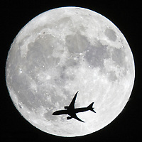 November 13, 2016-Winthrop,MA. A high altitude airliner headed for the Atlantic Ocean, exits the U.S> East Coast Sunday night, as Boston's Super Moon rises high in the sky. Staff photo by Mark Garfinkel
