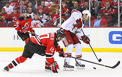 Mar 27, 2014; Newark, NJ, USA; Phoenix Coyotes center Kyle Chipchura (24) protects the puck from New Jersey Devils defenseman Peter Harrold (10) during the second period at Prudential Center.