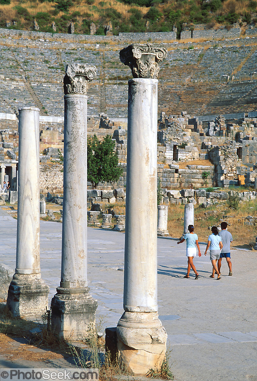 """Visitors walk beneath Corinthian order columns at the Great Theatre of Ephesus, in the Republic of Turkey. Published in the travel handbook """"Moon Istanbul & the Turkish Coast"""" by Jessica Tamtürk, Avalon Travel Publishing, 2010. The Great Theatre of Ephesus, the largest outdoor theatre in the ancient world, was begun during Hellenistic times (probably during the reign of Lysimachos in the third century BC), and was altered and enlarged from 41-117 AD by Roman emperors Claudius, Nero, and Trajan. The Greek builders dug out a space from Mount Pion (present-day Panayir Dagi) to fit the 30-meter (100-foot) high theater, which accommodated 25,000 people, or 10 percent of the population of Roman Ephesus at its peak. The theatre exhibited the fights of wild beasts and of men with beasts. In the 1st century AD, the Apostle Paul delivered a sermon condemning pagan worship in this theater. Subsequently, followers of the Ephesian cult of Artemis forced Paul and his followers out. Over several centuries, the Cayster River filled the harbor of Ephesus with silt, creating a malaria-infested swamp, pushing the sea 4 kilometers away and cutting off the city's commerce and wealth. By the 6th century AD, Emperor Justinian decided to build the Saint John Basilica 3 kilometers away, which effectively moved the city center to Selçuk."""
