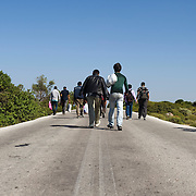 A group of Afghan refugees walking on the road between Mantamado and Mytilini. Most refugees land on the northern shores of the island and they walk for nine hours either to Mytilini port or to Moria  First Reception Centre..Everyday hundreds of refugees, mainly from Syria and Afghanistan, are crossing in small overcrowded inflatable boats the 6 mile channel from the Turkish coast to the island of Lesbos in Greece.