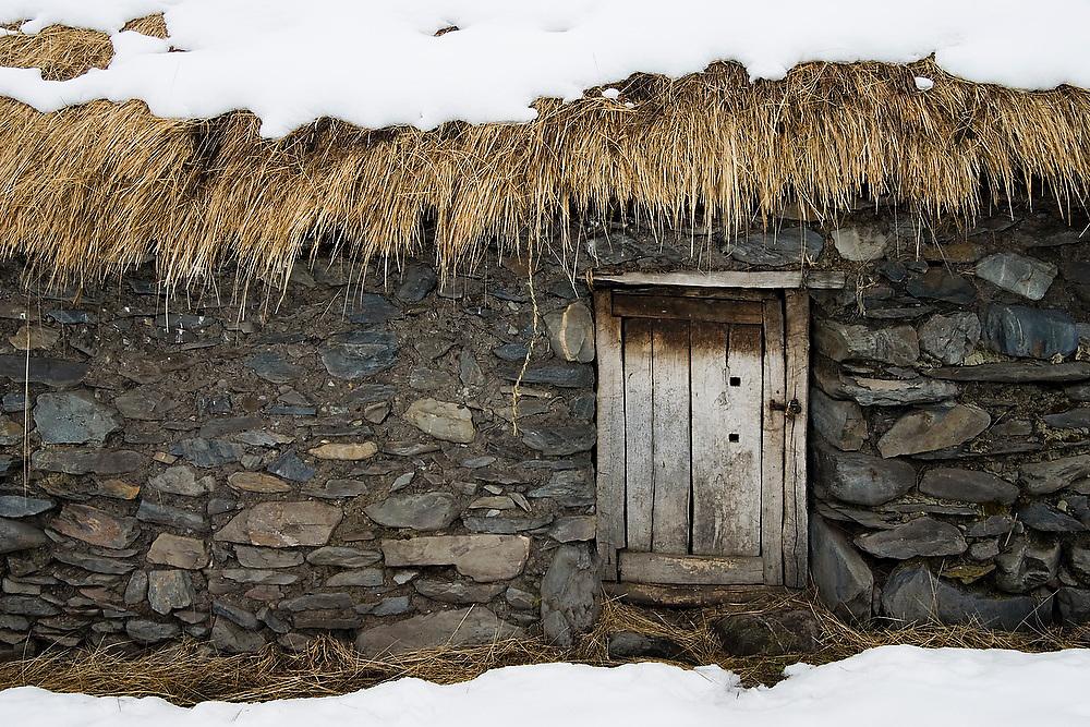 Small hut door in the alpaca herding village of the Q'eros people under snow, Cordillera de Paucartambo, Andes Mountains, Peru.