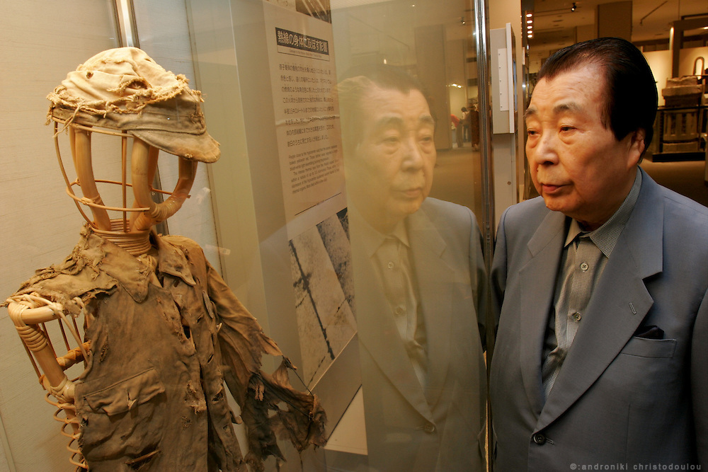 AKIHIRO TAKAHASHI.  Hiroshima A-Bomb survivor.  Former director of Hiroshima Peace Memorial Museum. Photo: inside the museum, in front of the uniform that a close friend who died in the bombing was wearing.
