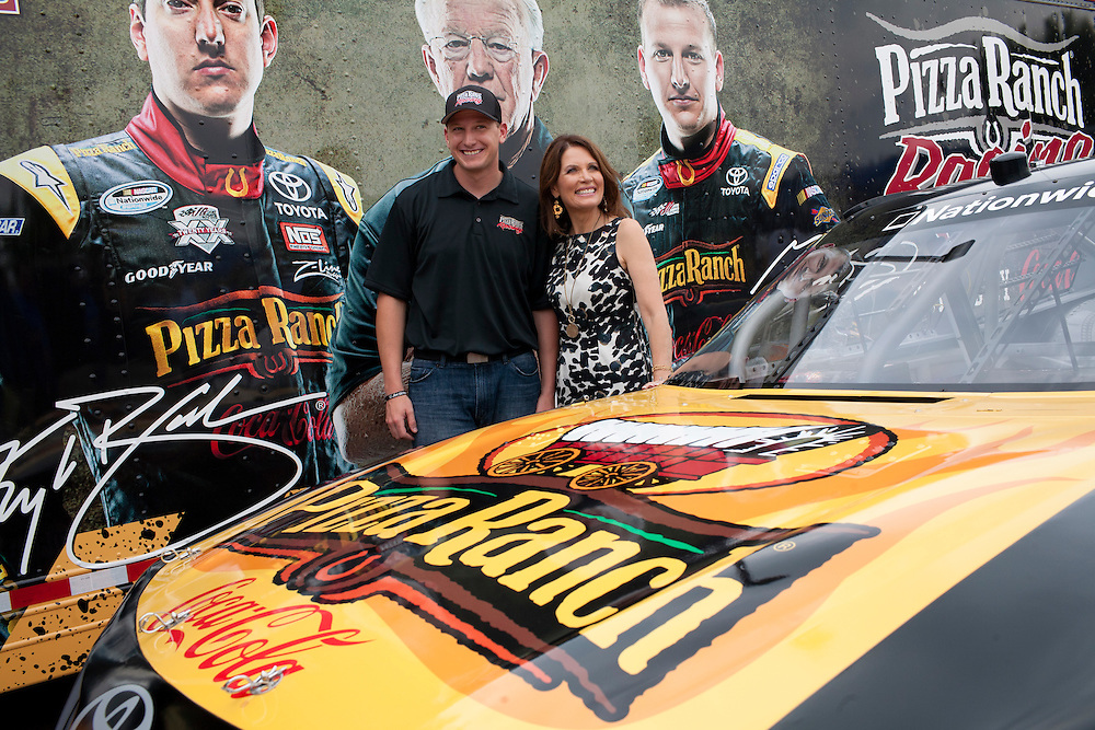 Republican presidential hopeful Michele Bachmann, right, poses with driver Michael McDowell of Joe Gibbs Racing after a campaign stop on Friday, August 5, 2011 in Newton, IA.