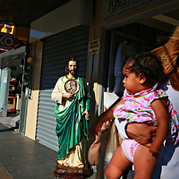 A Mom and her daughter walk by religious Icons for sale at a shop in Downtown Tijuana, Mexico on Wednesday, October 8, 2014.(Photo by Sandy Huffaker for The New York Times)