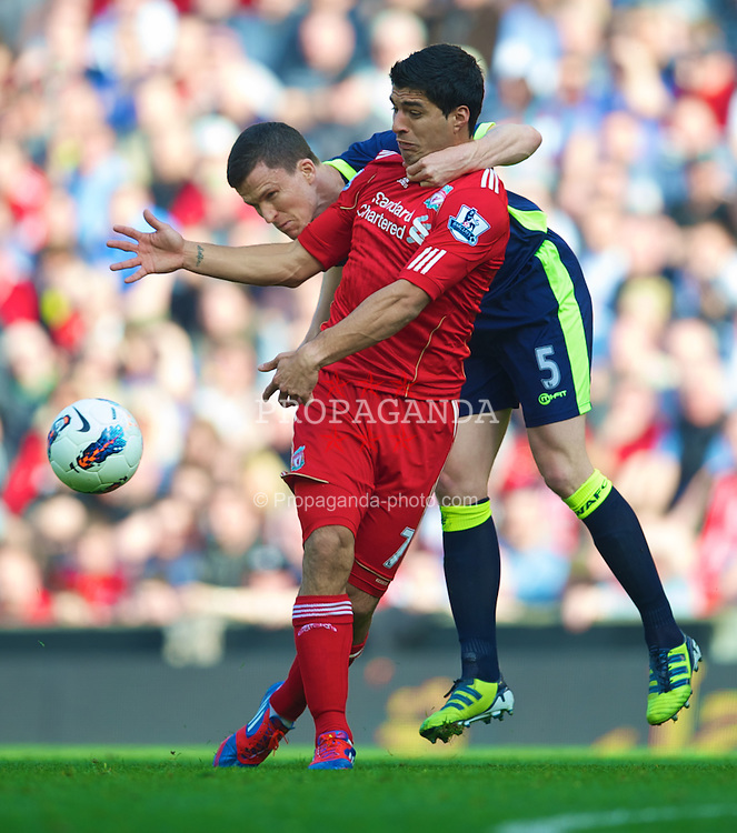 LIVERPOOL, ENGLAND - Saturday, March 24, 2012: Liverpool's Luis Alberto Suarez Diaz is man-handled by Wigan Athletic's Gary Caldwell during the Premiership match at Anfield. (Pic by David Rawcliffe/Propaganda)