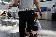 Female security operative feels around a male passenger's leg for suspect items during search at Heathrow Airport's T5