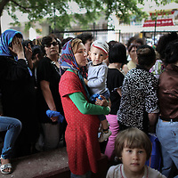 An Afghan woman waiting in the line with her children. Immigrants are served after 2:30 went the service reserved for Greek only finishes.