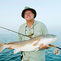 Fly fisherman shows his near record Redfish caught in the Laguna Madre off the Texas Gulf Coast.