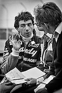 Italian Formula One driver Michele Alboreto is shown here being de-briefed after practice for the 1982 Detroit Grand Prix by Candy Team Tyrrell engineer Brian Lisles and team principle Ken Tyrrell. He would fail to finish the event, but would take Benetton Team Tyrrell to victory in the 1983 Detroit Grand Prix.<br /> <br /> With no sensors, telemetry, on-board communications, and assorted &quot;black boxes&quot; common with today's Formula One machines, racing engineers and drivers from 1950's to the late 1980's have had to develop their own &quot;language&quot; for describing on-track power, traction, grip and transient response and determining how to make improvements. <br /> <br /> Once those changes were made, teams counted on their drivers to use their tremendous reflexes, their accumulated knowledge and the best guesses of their engineer to take the car to the new limits to determine if the changes were an improvement. <br /> <br /> It was one of their two primary tasks: race what they were given; to carry the car on their backs and push it out to the edge of control and beyond&hellip;and get points. Sometimes they succeeded, sometimes they didn&rsquo;t. And if they didn&rsquo;t they were gone, or worse.