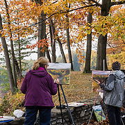 """Painters capture gorgeous fall clors. In Letchworth State Park, renowned as the """"Grand Canyon of the East,"""" the Genesee River roars northeast through a gorge over three major waterfalls between cliffs as high as 550 feet, surrounded by diverse forests which turn bright fall colors in the last three weeks of October. The large park stretches 17 miles between Portageville and Mount Morris in the state of New York, USA. Drive or hike to many scenic viewpoints along the west side of the gorge. The best walk is along Gorge Trail #1 above Portage Canyon from Lower Genesee Falls (70 ft high), to Inspiration Point, to Middle Genesee Falls (tallest, 107 ft), to Upper Genesee Falls (70 ft high). High above Upper Falls is the railroad trestle of Portageville Bridge, built in 1875, to be replaced 2015-2016. Geologic history: in the Devonian Period (360 to 420 million years ago), sediments from the ancestral Appalachian mountains eroded into an ancient inland sea and became the bedrock (mostly shales with some layers of limestone and sandstone plus marine fossils) now exposed in the gorge. Genesee River Gorge is very young, as it was cut after the last continental glacier diverted the river only 10,000 years ago. The native Seneca people were largely forced out after the American Revolutionary War, as they had been allies of the defeated British. Letchworth's huge campground has 270 generously-spaced electric sites."""