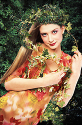 A fantasy fashion photograph of a young woman in a floral dress and with her head adorned by leaves. This is a fantasy conceptual art depicting a fairy.